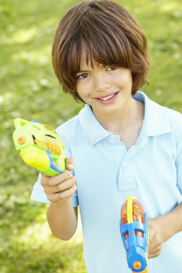 Free Young Boy Playing With Water Pistols In Park Royalty Free Stock Image - 54953296