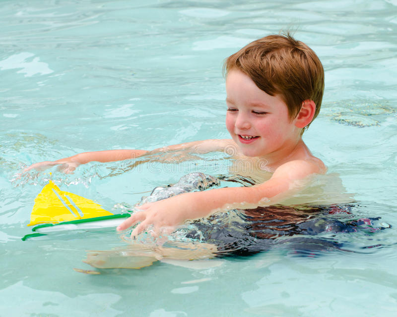 Young boy plays with toy boat while in pool royalty free stock photography