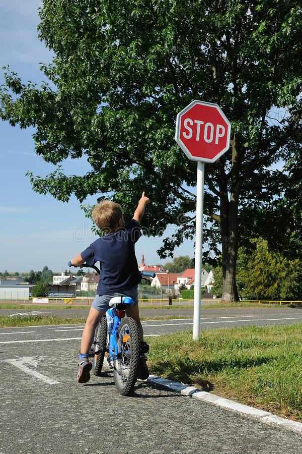 Young boy pointing to stop sign