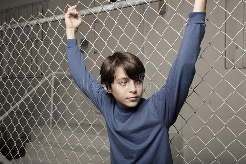 Young boy posing on a chain-link fence stock photography