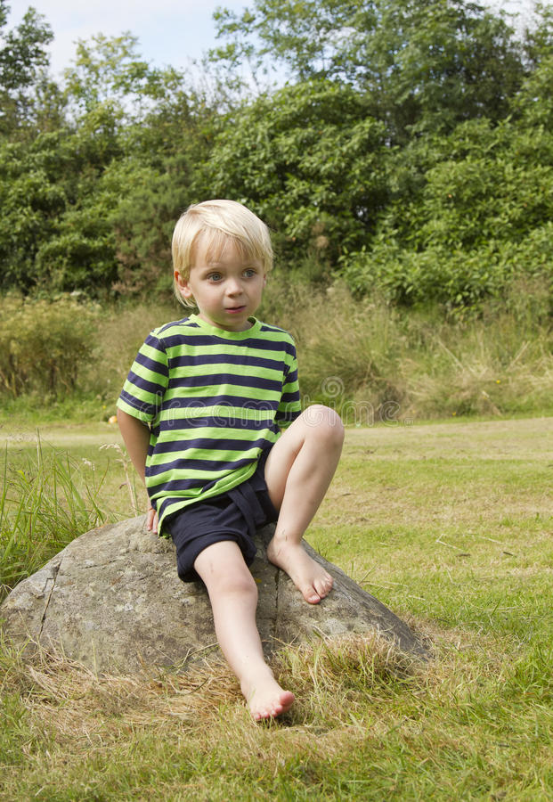 Young boy posing on a rock royalty free stock photo