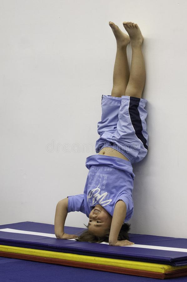 A young boy practices standing on his head in acrobat school royalty free stock image