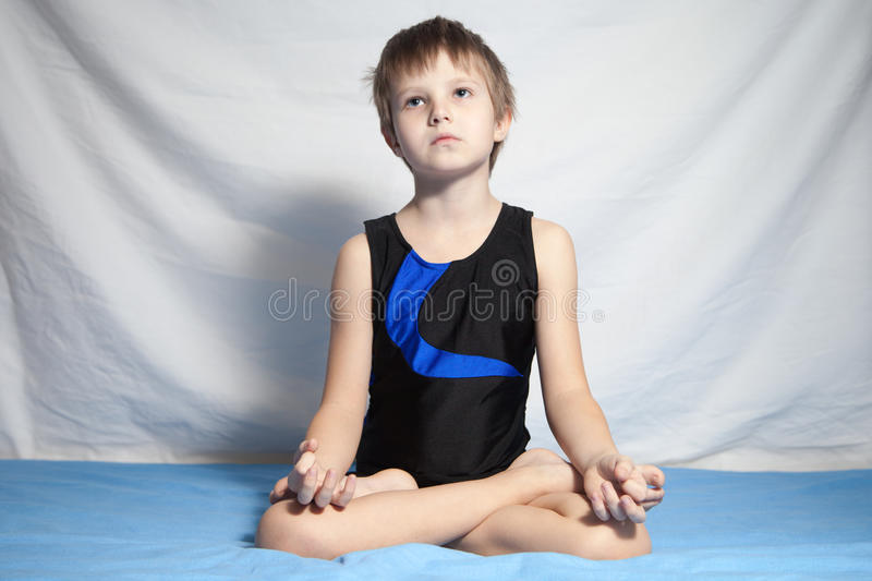 Young boy practices yoga stock images