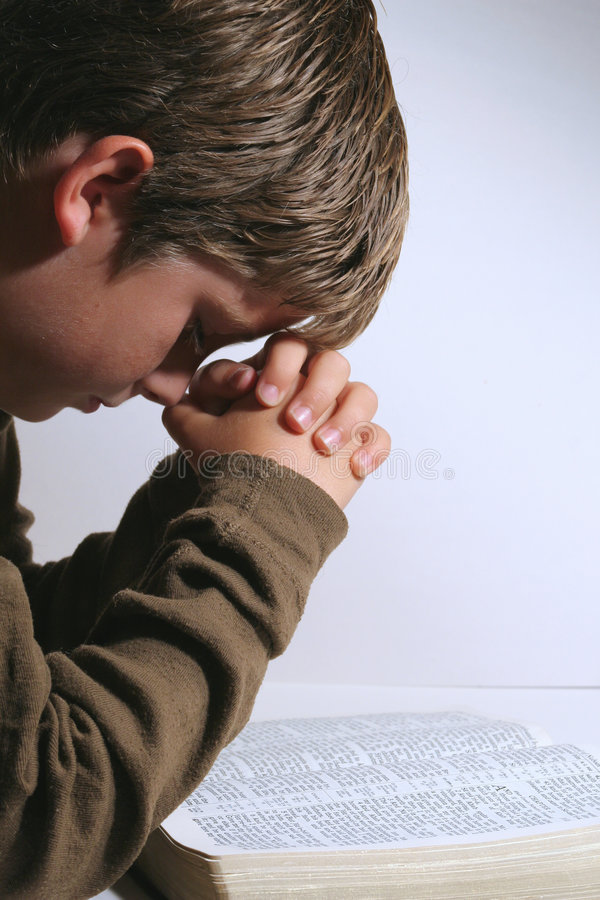 Young boy praying over his bible stock photo