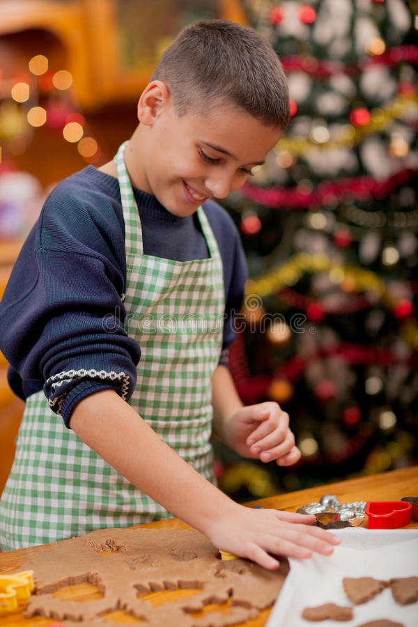 Young boy preparing Christmas cookies. Boy baking in kitchen Christmas cakes royalty free stock images