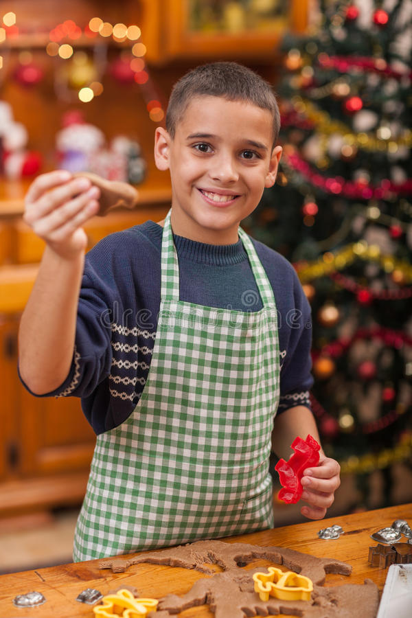Young boy preparing Christmas cookies. Boy baking in kitchen Christmas cakes royalty free stock image