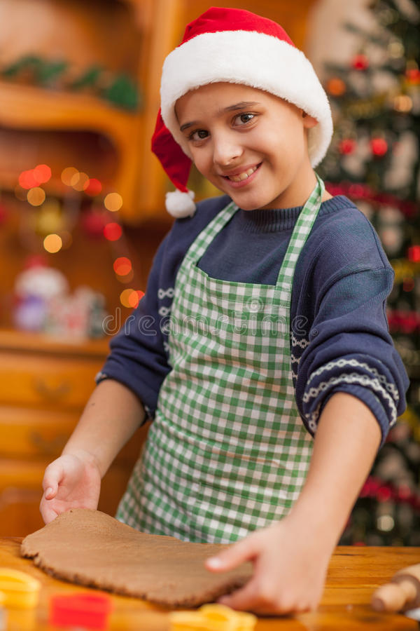 Young boy preparing Christmas cookies. Boy baking in kitchen Christmas cakes stock images
