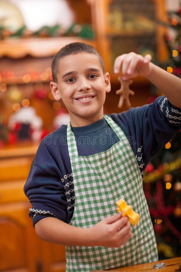 Young boy preparing Christmas cookies. Boy preparing in kitchen Christmas cakes stock photo