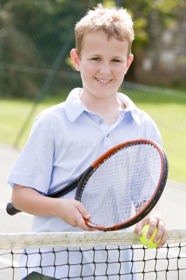 Young boy with racket on tennis court smiling royalty free stock images