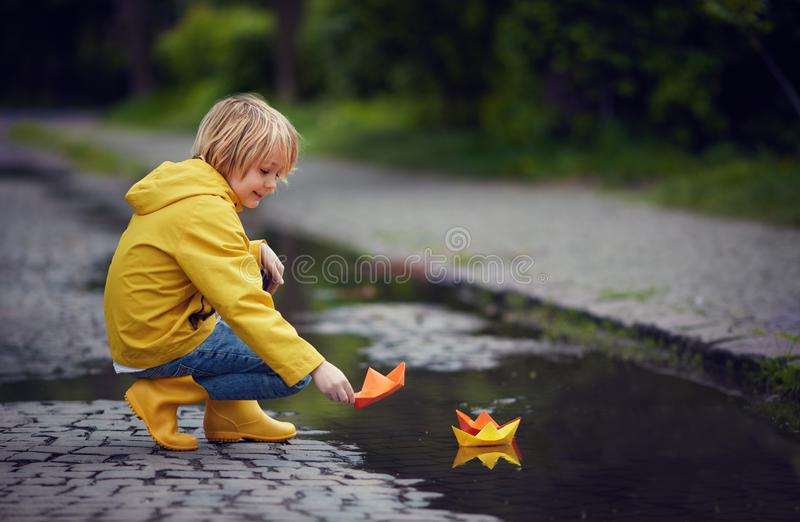 Young boy in rain boots and coat is putting paper boats on the water, at spring rainy day stock photography
