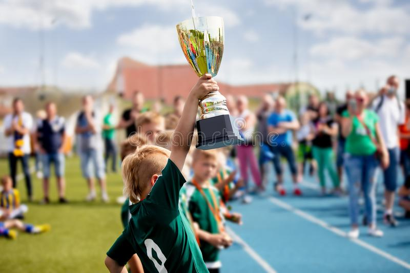 Young Boy Raising Golden Football Cup. Winning Youth Football Team Celebrating Success stock images