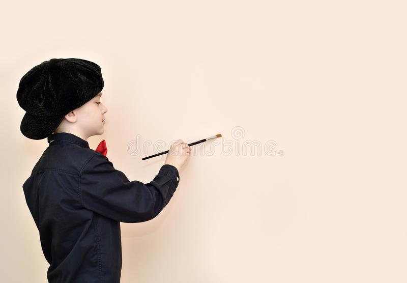 Young boy with the paint brush painting on the wall stock images