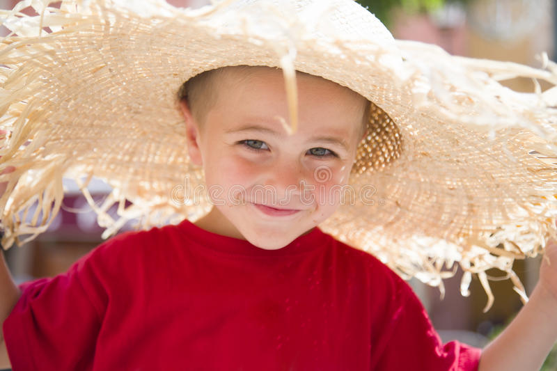 Young boy in red shirt, with large sun hat stock photo