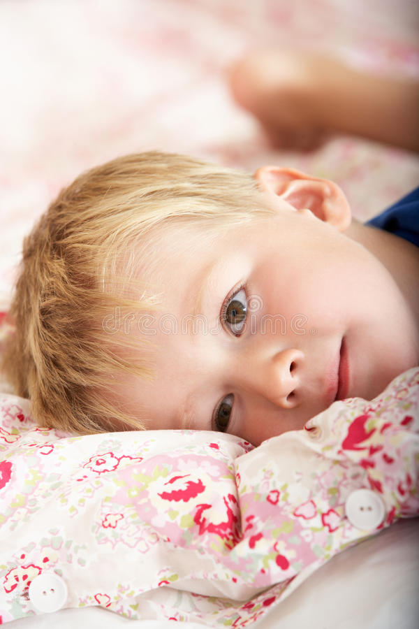 Download Young Boy Relaxing On Bed stock photo. Image of year - 26615952