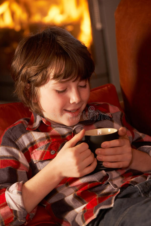 Download Young Boy Relaxing With Hot Drink By Cosy Log Fire Stock Image - Image: 24424127