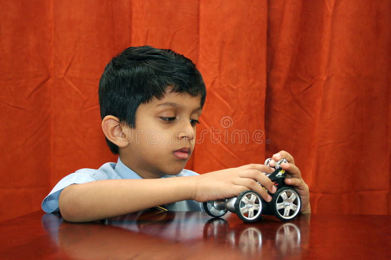 Young boy repairing toy car royalty free stock photo
