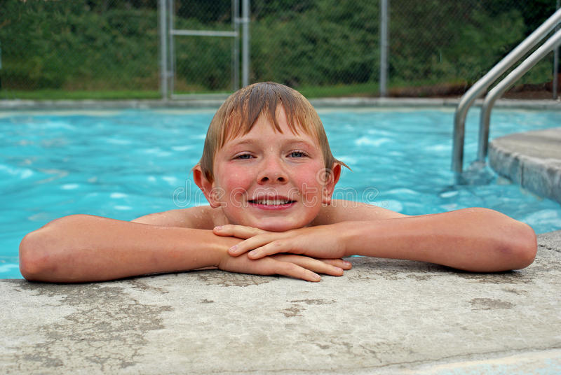 Young boy resting after swimming. A youngBoy resting by the swimming pool with a broad smile and look of delight on his face rest beside the swimming pool i in royalty free stock photos