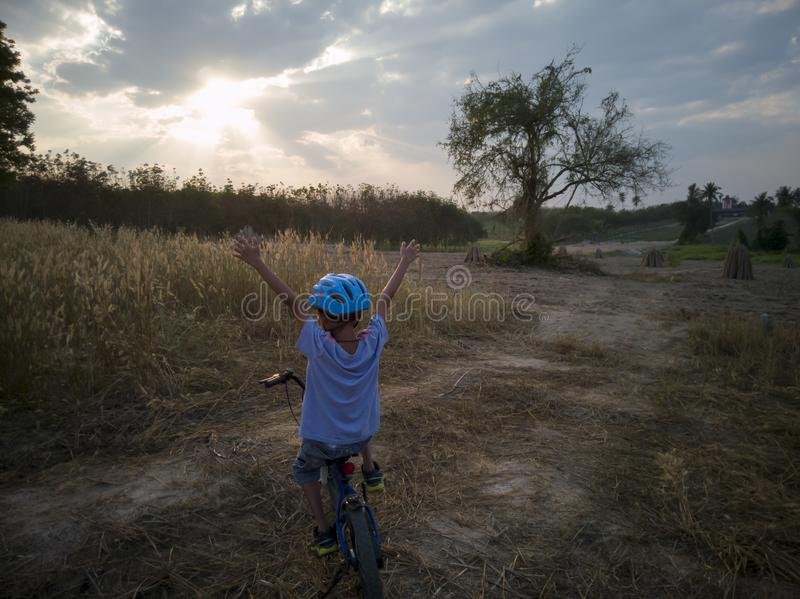 Young Boy ride bicycle happy in the evening with sunset. stock photo