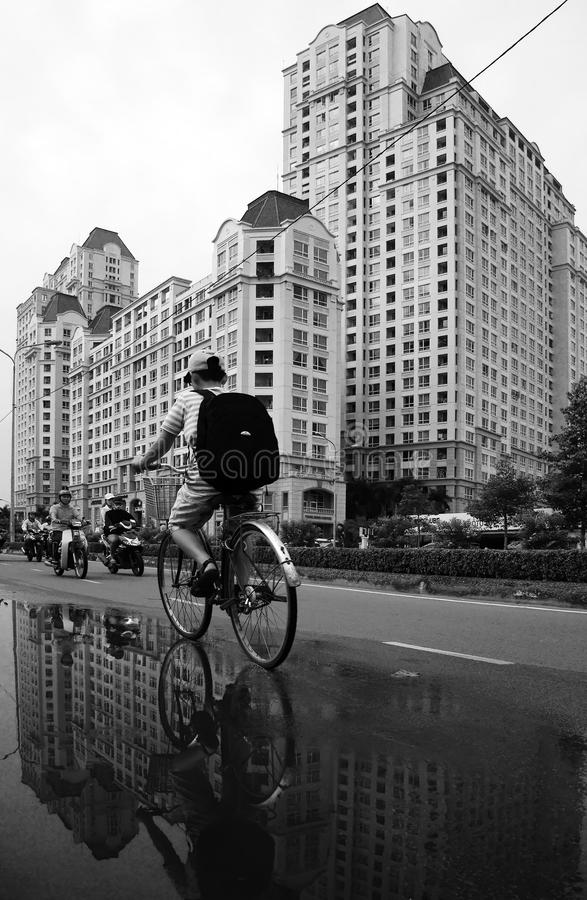 Young boy ride bicycle with high-rise building background stock photography