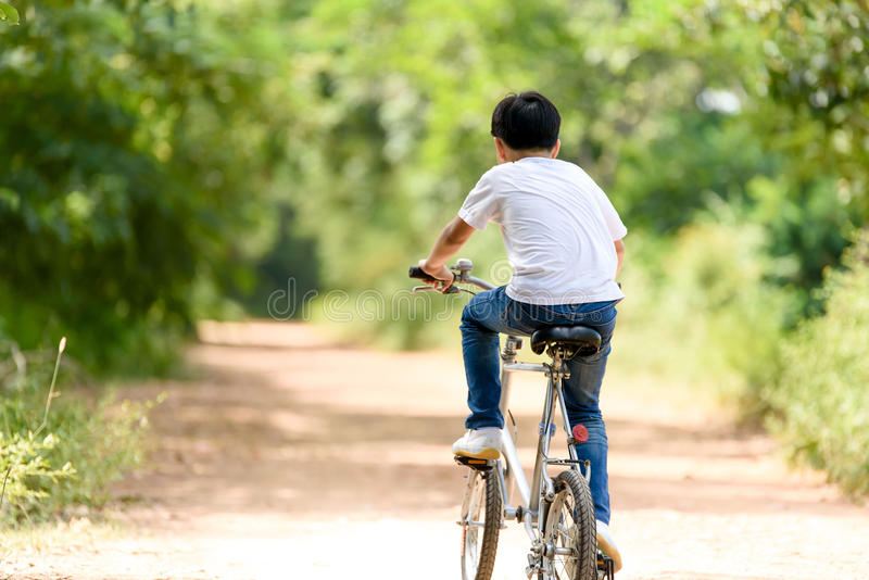 Young boy ride bicycle. Young Thai boy ride bicycle hand on the road in the park stock image