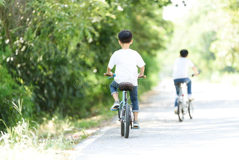 Young boy ride bicycle. Young Thai boy ride bicycle on the road in the park royalty free stock image