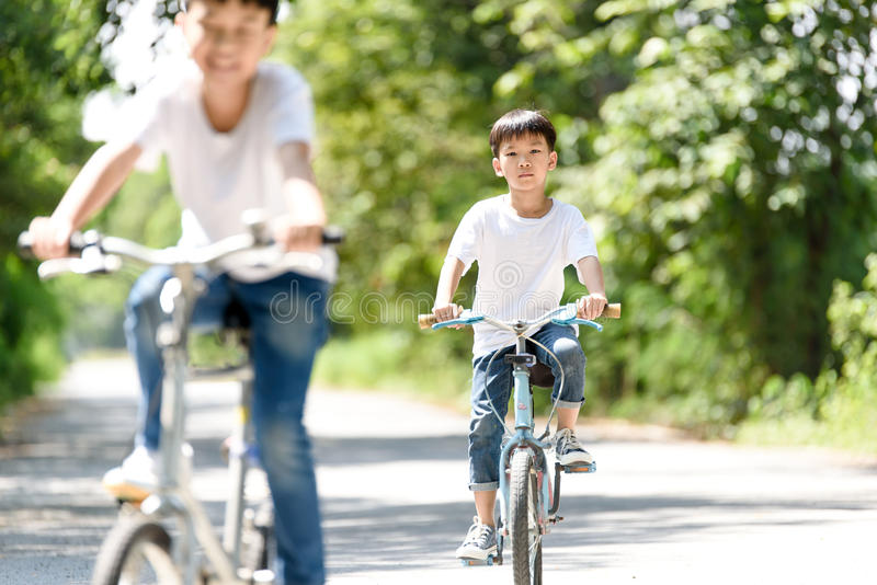 Young boy ride bicycle. Young Thai boy ride bicycle on the road in the park royalty free stock photography