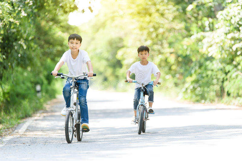 Young boy ride bicycle. Young Thai boy ride bicycle on the road in the park royalty free stock photos