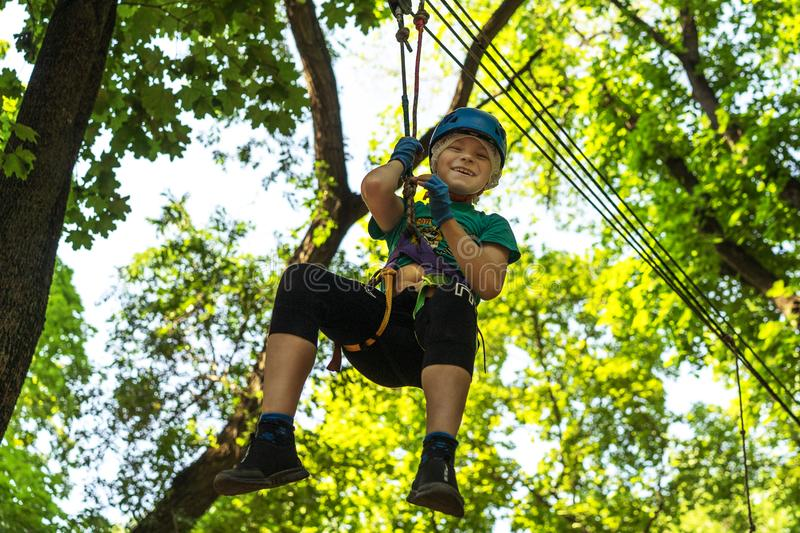 Young boy rolling down the cable route high among trees, extreme sport in adventure park royalty free stock photos