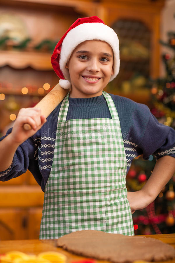 Young boy with rolling pin preparing Christmas cookies. Boy with rolling pin baking in kitchen Christmas cakes stock image