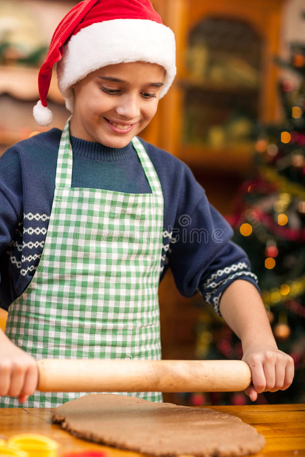Young boy with rolling pin preparing Christmas cookies. Boy with rolling pin baking in kitchen Christmas cakes stock photo
