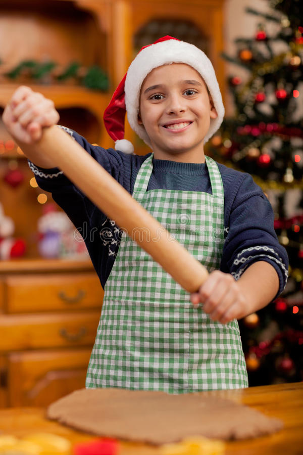 Young boy with rolling pin preparing Christmas cookies. Boy with rolling pin baking in kitchen Christmas cakes royalty free stock photography