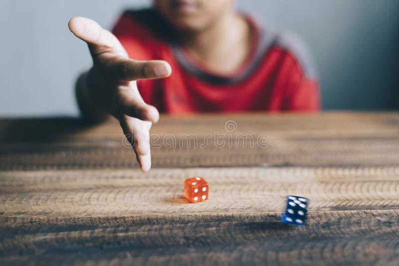 Young boy rolling / throwing a dice royalty free stock images