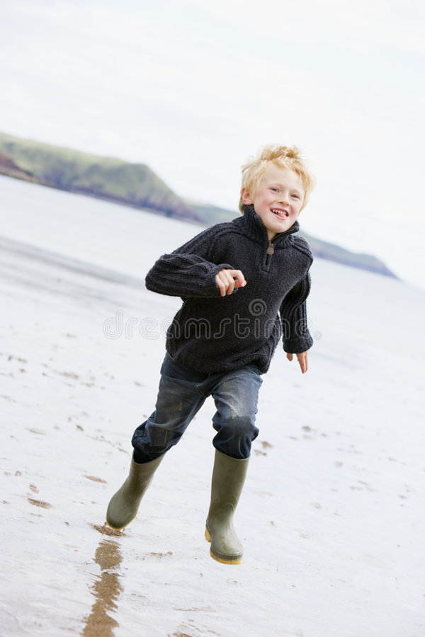 Young boy running on beach smiling stock photo
