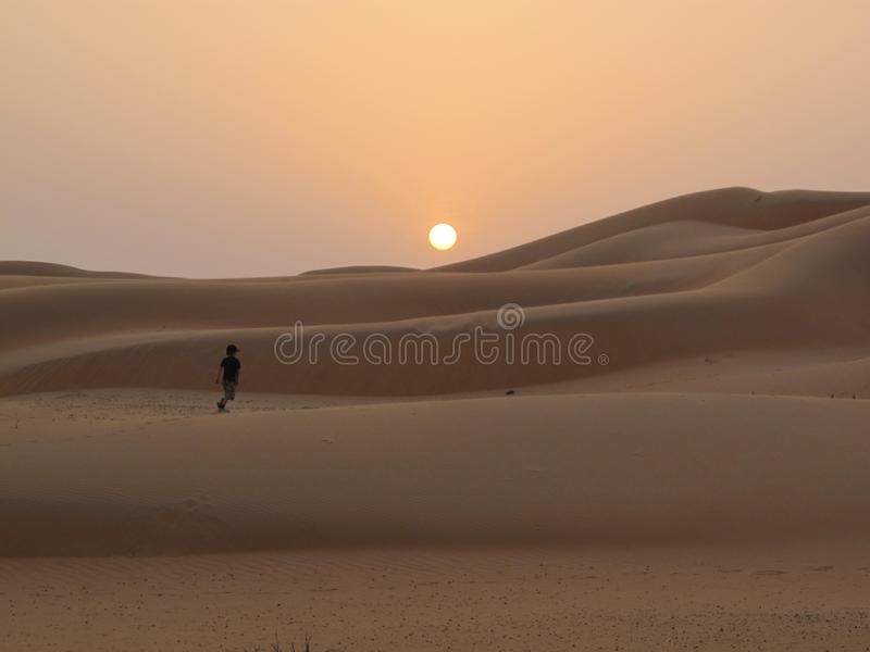 Young boy running into a desert sunset royalty free stock photography