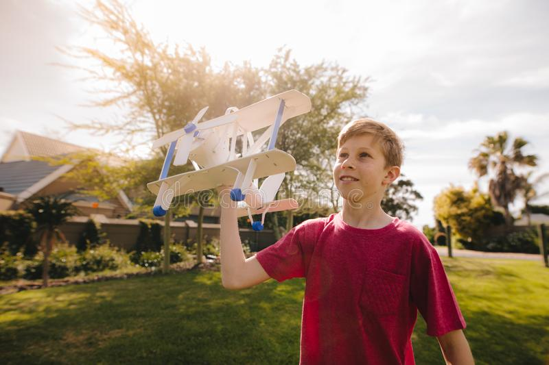 Young boy running with a toy airplane. Boy having fun playing with white color toy plane outdoors. Kid playing with a toy airplane on a sunny day stock photos