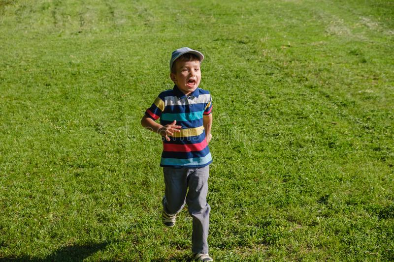 Young boy runs in a green field. Cute child running across park outdoors grass. Smiling royalty free stock photo