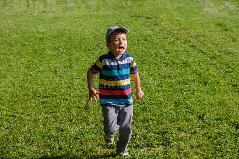 Young boy runs in a green field. Cute child running across park outdoors grass. Young boy runs in a green field. Cute child running across park outdoors grass royalty free stock image