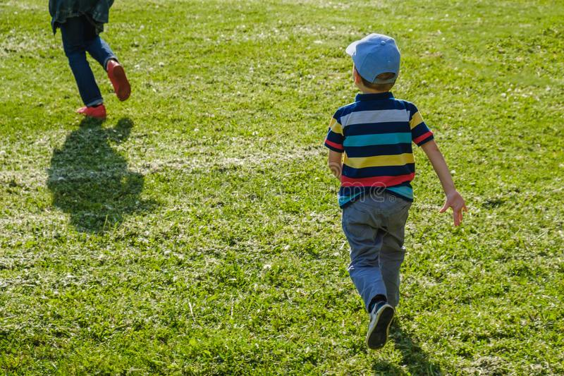 Young boy runs in a green field. Cute child running across park outdoors grass. Young boy runs with his mother in a green field. Cute child running across park royalty free stock images