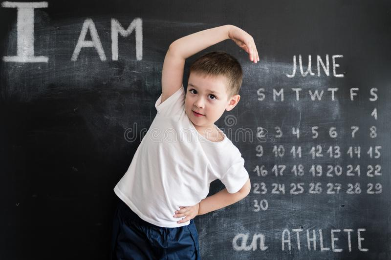 Young boy`s doing athletic exersices near blackboard. Young athlete. Creative design concept for 2019 calendar. June.  royalty free stock photo