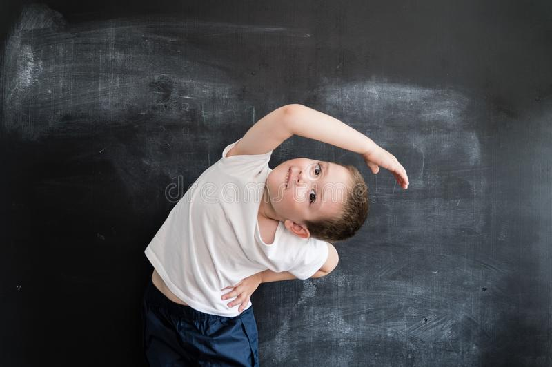 Young boy`s doing athletic exersices near blackboard. Young athlete. Creative design concept for 2019 calendar. Young boy`s doing athletic exersices near stock photos