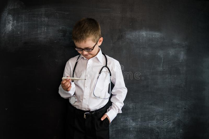 Young boy`s standing near blackboard checking thermometer. Young doctor. Creative design concept of future profession. royalty free stock photo