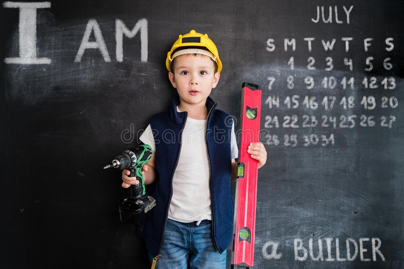 Young boy`s standing with screwdriver near blackboard. Young builder. Creative design concept for 2019 calendar. July.  stock image