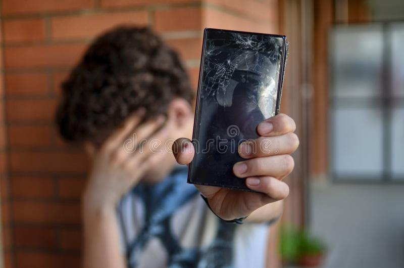 Young boy, sad and desperate for his smartphone stock image