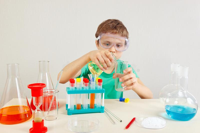 Young boy in safety goggles doing chemical experiments in laboratory. Young boy in safety goggles doing chemical experiments in the laboratory royalty free stock photos