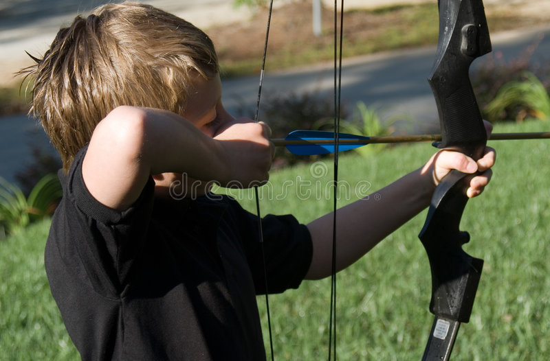Young Boy Shooting Arrow stock photography