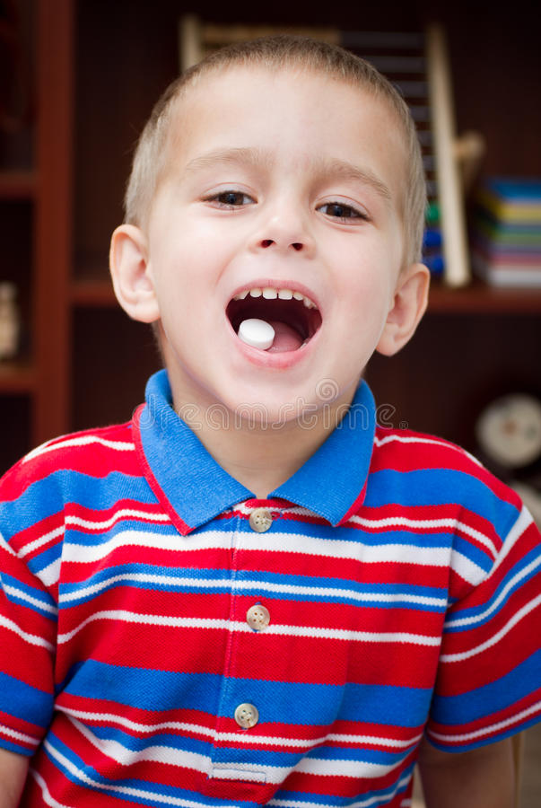 Young boy showing a capsule royalty free stock photos