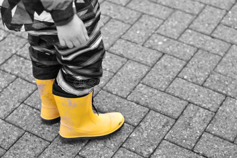 Junge mit gelben Gummistiefeln royalty free stock image