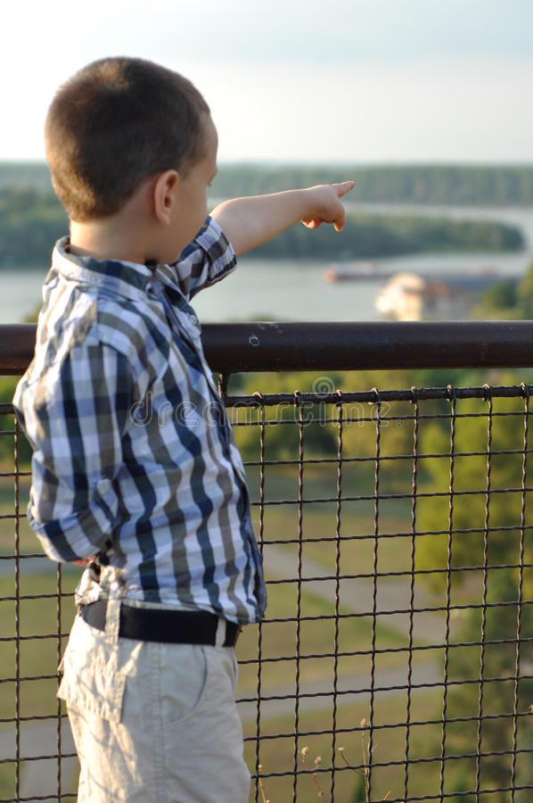Young boy shows to the river stock photos