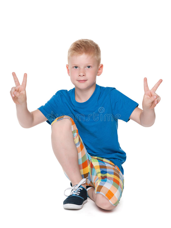 Young boy shows a victory sign royalty free stock photography