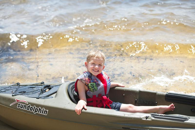 A young boy sits in a kayak along the water. A preschool boy sits in a kayak on the water.  He has a smile on his face and he is wearing a life jacket royalty free stock image